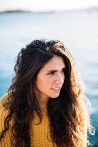 Portrait of young woman looking away while sitting on pier.Summertime
